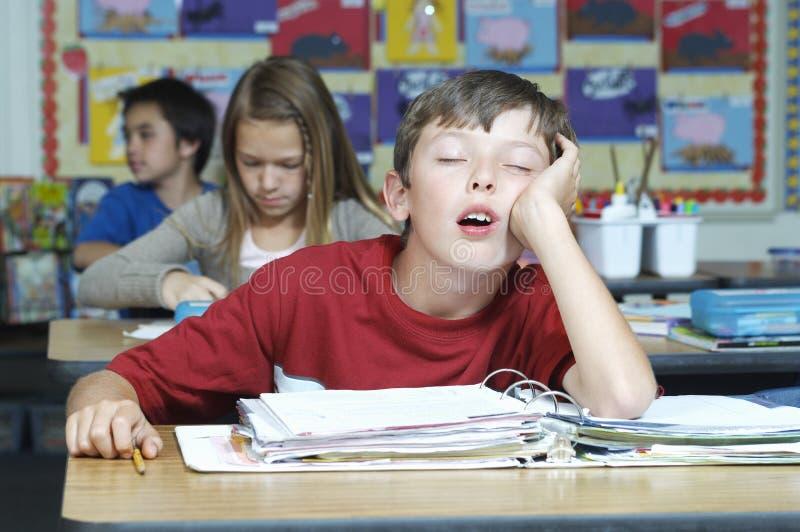 Pojke som sover i klassrum royaltyfria foton