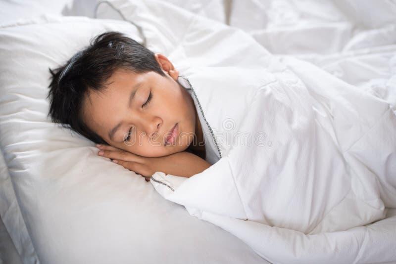 Pojke som sover på säng med det vita arket och kudden royaltyfria foton