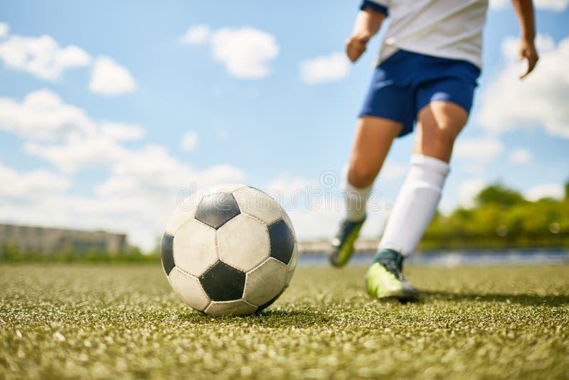 Pojke som sparkar bollen i fotboll royaltyfri foto