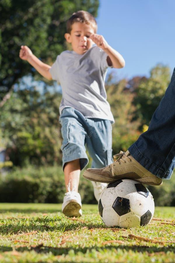 Pojke som sparkar fotbollen royaltyfria bilder