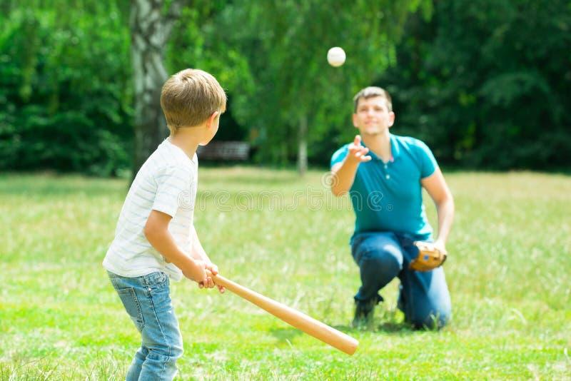 Pojke som spelar baseball med hans fader royaltyfri fotografi