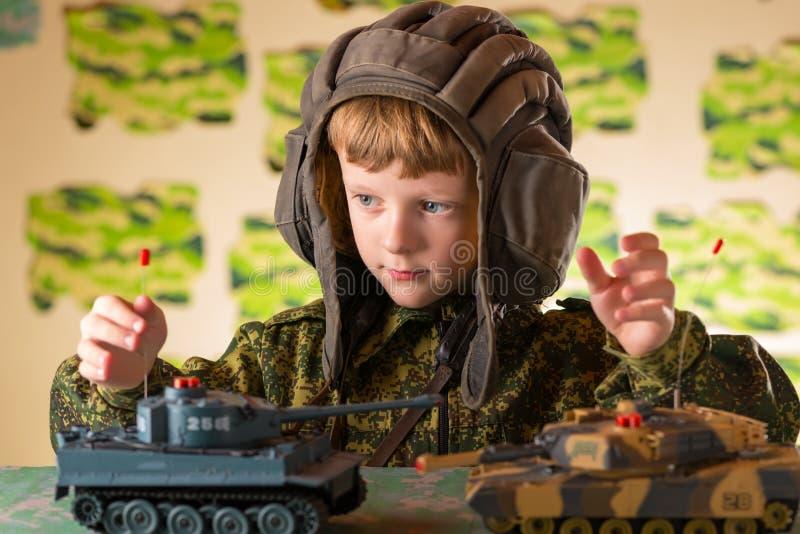 Pojke som spelar den militära behållaren för leksak royaltyfria foton