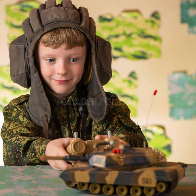 Pojke som spelar den militära behållaren för leksak royaltyfri bild