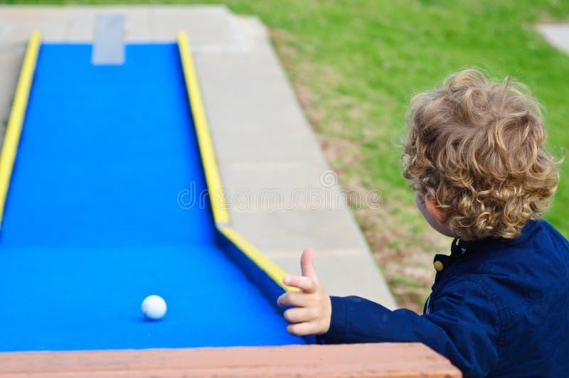 Pojke som spelar i minigolf arkivbild