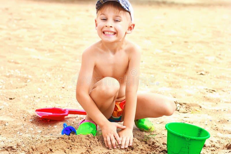 Pojke som spelar i sanden på en tropisk strand arkivfoton