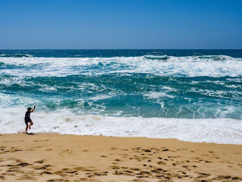 Pojke som spelar i stora vågor på Montara den statliga stranden arkivbild