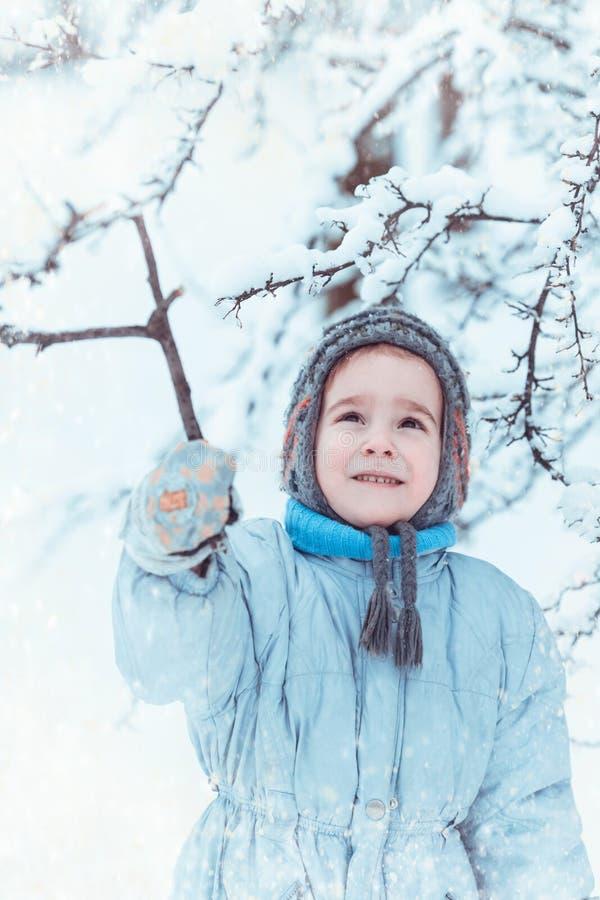 Pojke som spelar i vinterskog royaltyfri bild