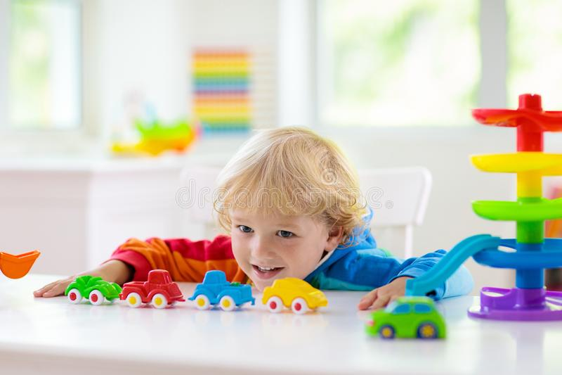 Pojke som spelar leksakbilar Unge med leksaker barn och bil royaltyfri fotografi
