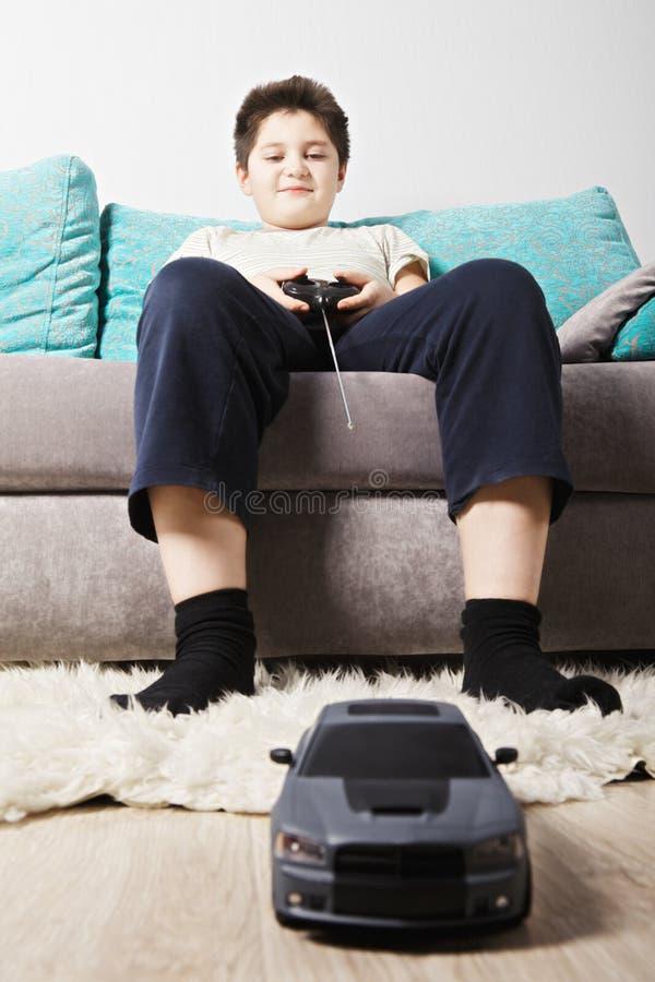 Pojke som spelar leksakbilen arkivbild