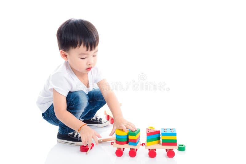 Pojke som spelar leksaken på golvet över vit bakgrund royaltyfri bild