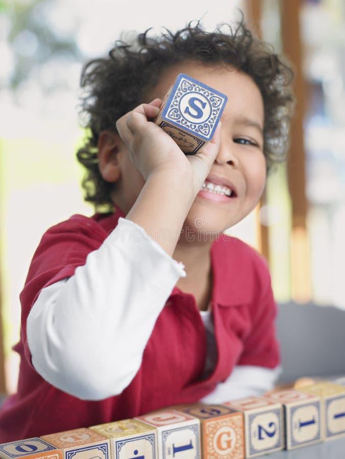 Pojke som spelar med alfabetkvarteret i grupp royaltyfria foton