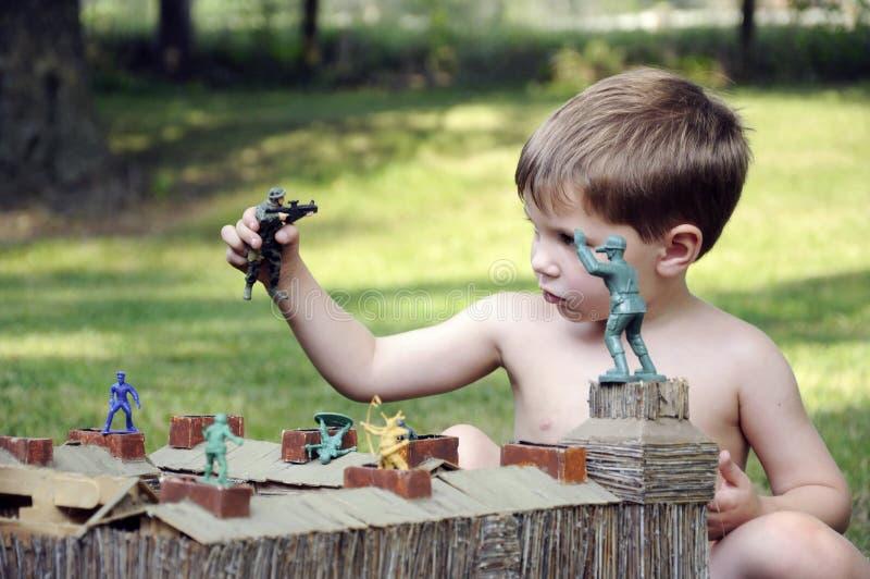 Pojke som spelar med arméleksaker i fort arkivfoton