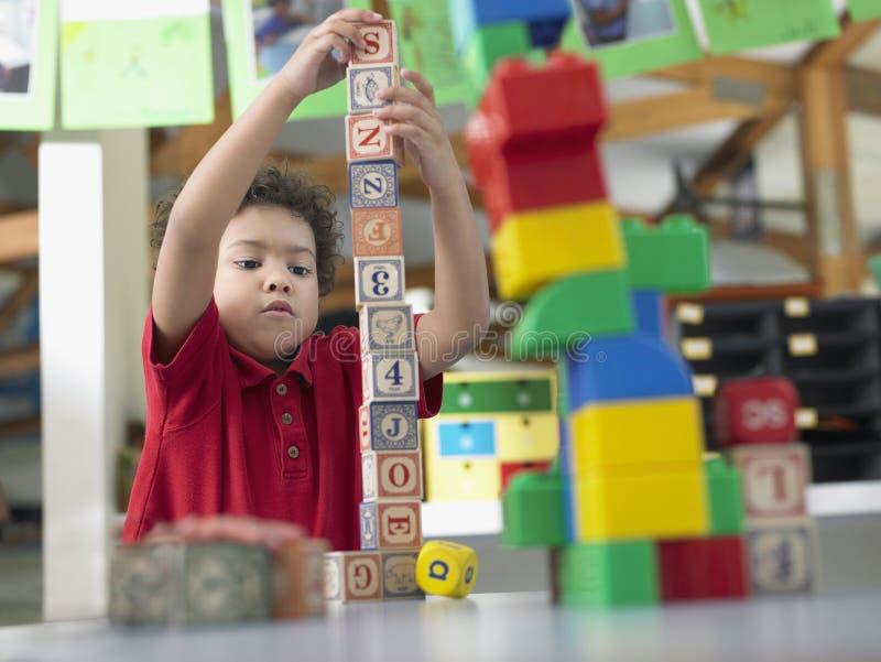 Pojke som spelar med byggnadskvarter i grupp royaltyfri fotografi