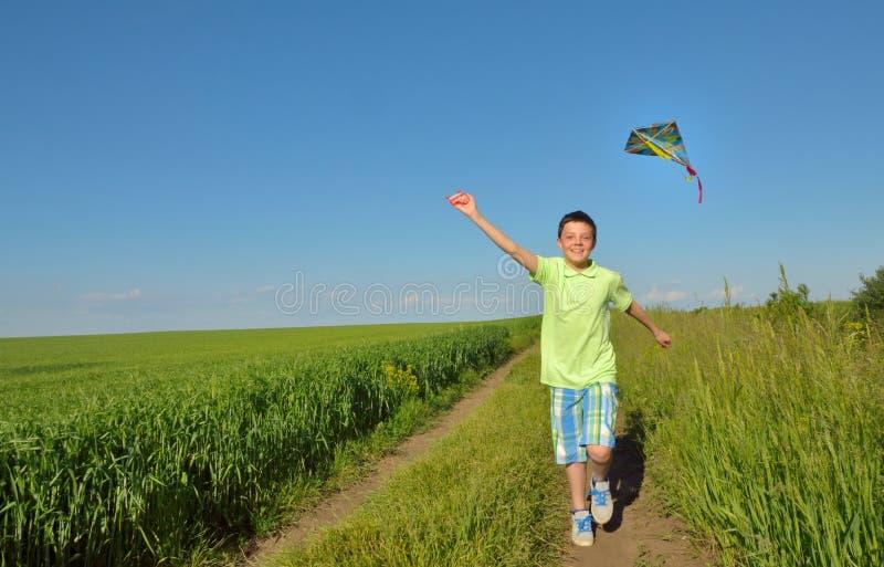 Pojke som spelar med draken på greenfield royaltyfri foto