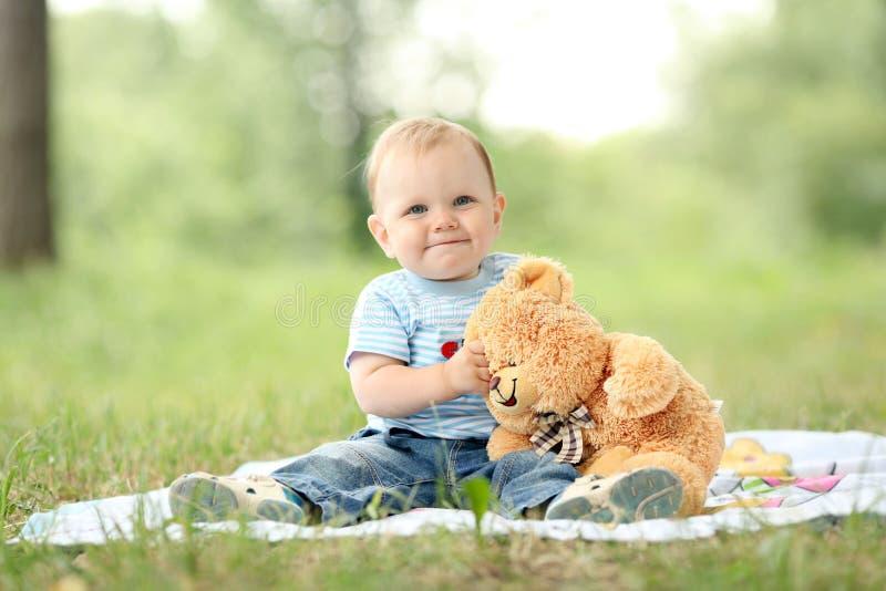 Pojke som spelar med en nallebjörn i gräset fotografering för bildbyråer