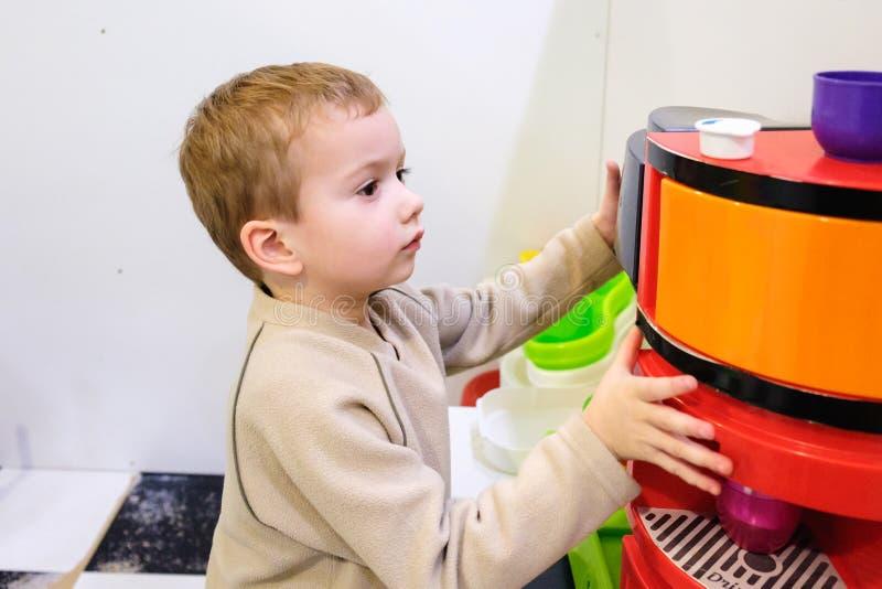 Pojke som spelar med ett leksakkök i barnrum eller dagis arkivfoto