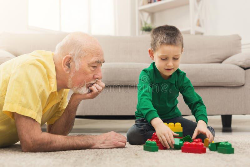 Pojke som spelar med farfadern i byggnadssats arkivfoton
