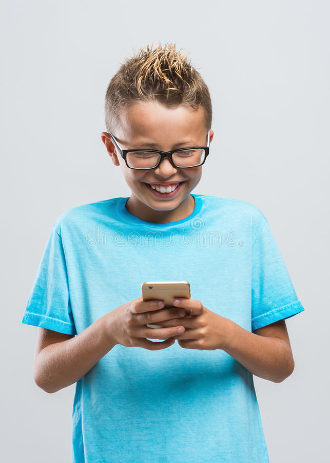 Pojke som spelar med hans smarta telefon fotografering för bildbyråer