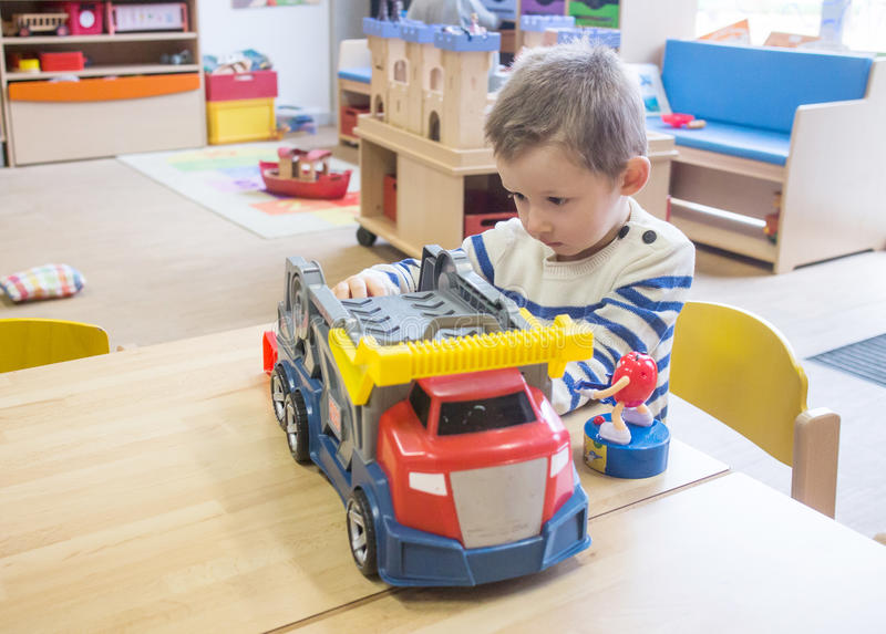 Pojke som spelar med leksaker i dagis royaltyfri bild