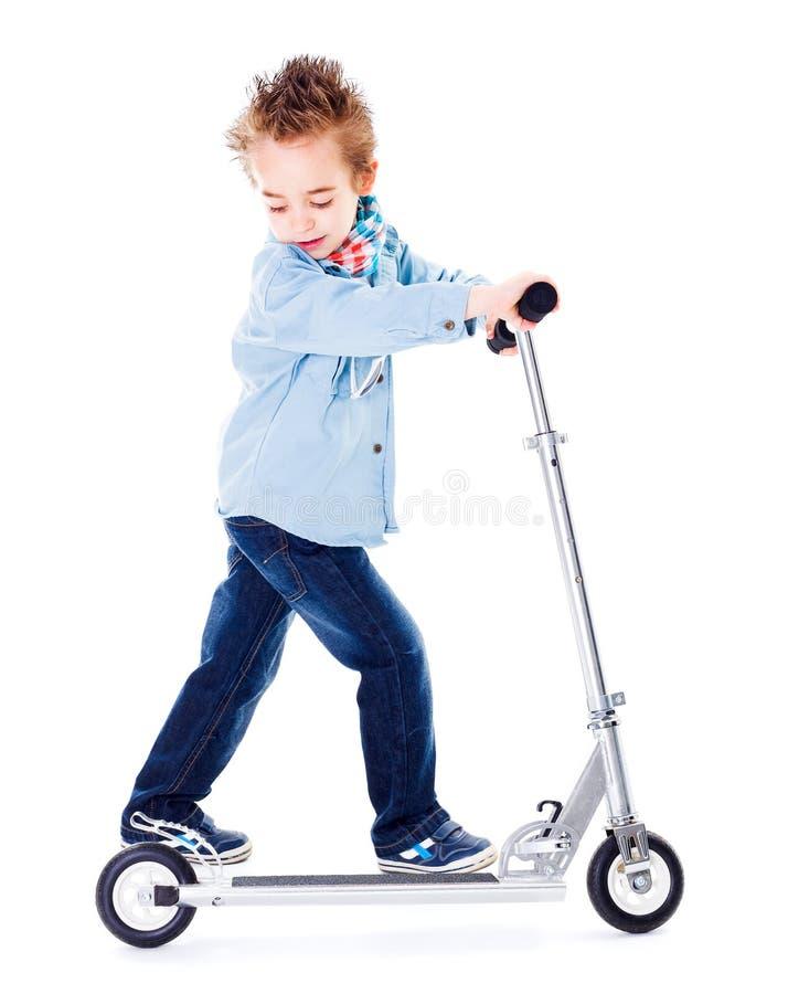 Pojke som spelar med sparkcykeln royaltyfri fotografi