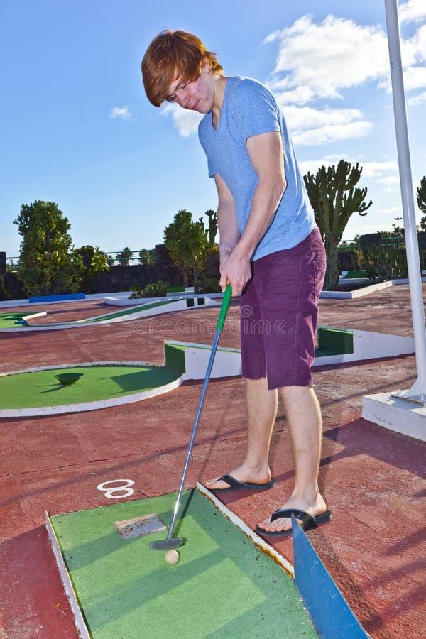 Pojke som spelar mini- golf i kursen arkivbilder