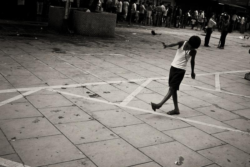 Pojke som spelar på gatan arkivbild