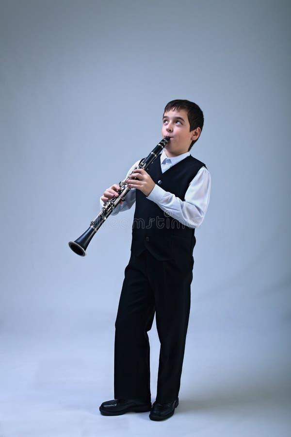 Pojke som spelar på klarinetten fotografering för bildbyråer