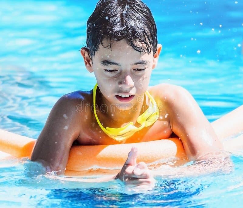 Pojke som spelar på simbassängen som trycker på vattnet med händer a royaltyfri foto