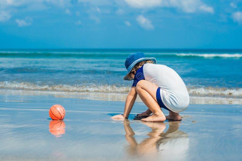 Pojke som spelar på stranden i vattnet arkivbild