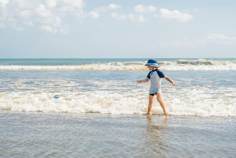 Pojke som spelar på stranden i vattnet arkivfoto