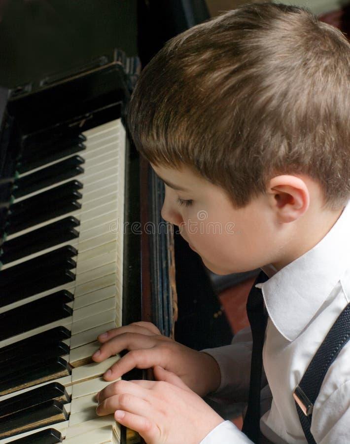 pojke som spelar pianot royaltyfri bild
