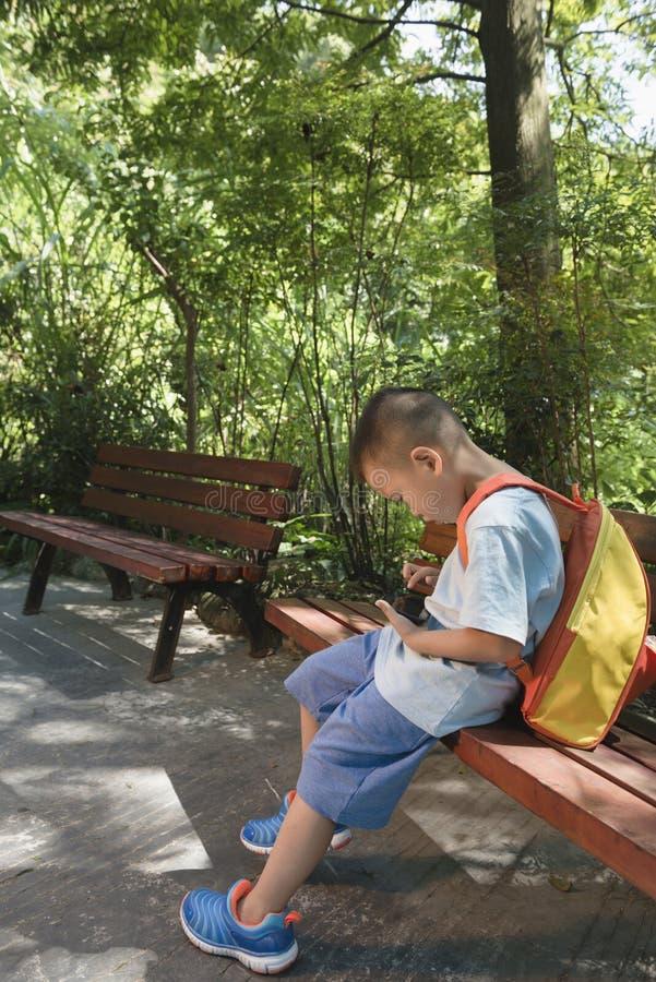 Pojke som spelar smartphonen royaltyfri fotografi