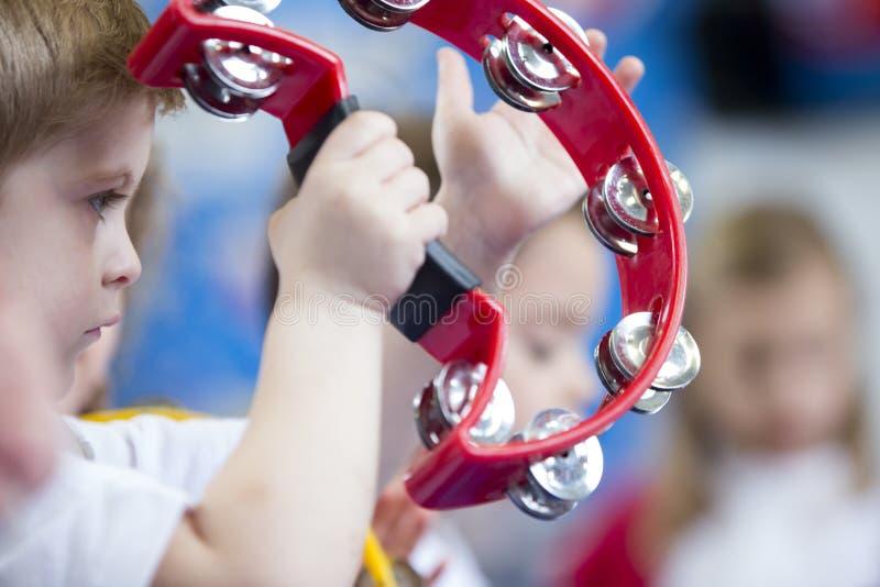 Pojke som spelar tamburin på barnkammaren royaltyfria bilder