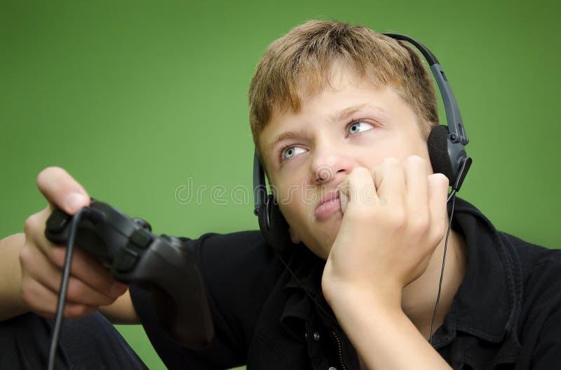 Pojke som spelar videospel - UTTRÅKAT TRÖTT royaltyfri bild
