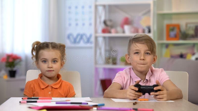 Pojke som spelar videospelet genom att använda konsolen, syster som ser skärmen och att ha gyckel royaltyfri fotografi