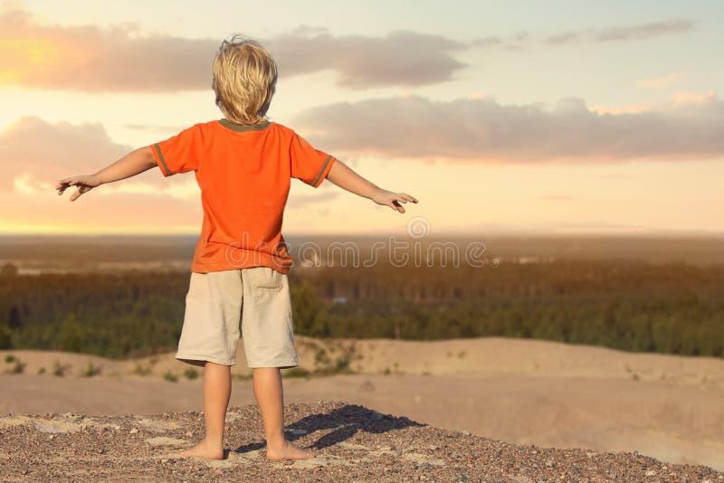 Pojke som st?r och h?ller ?gonen p? solnedg?ngen i sandberget royaltyfri bild