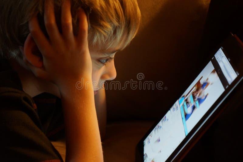 Pojke som stirrar på iPadminnestavladatoren arkivfoton