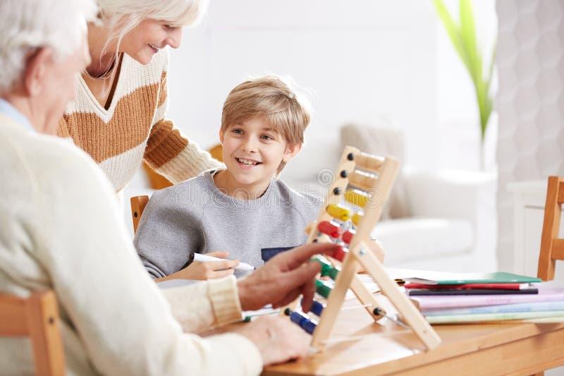 Pojke som studerar matematik med morföräldrar arkivbild