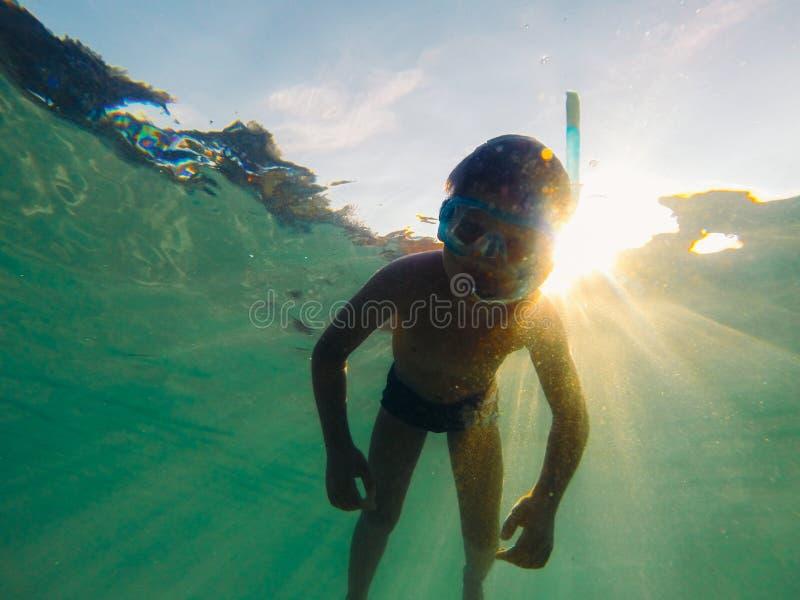 Pojke som svävar i undervattens- arkivfoto
