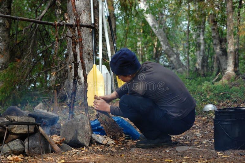 Pojke som tänder en lägerbrand royaltyfri fotografi