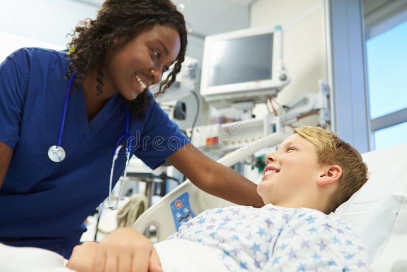 Pojke som talar till den kvinnliga sjuksköterskan In Emergency Room arkivfoton