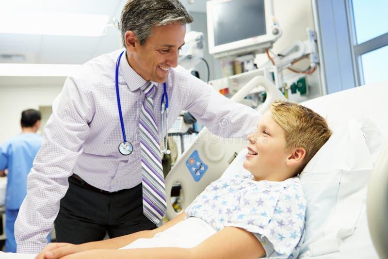 Pojke som talar till den manliga konsulenten In Emergency Room arkivbilder