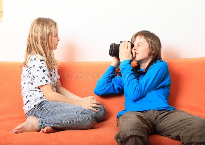 Pojke som tar fotoet av flickan royaltyfri bild