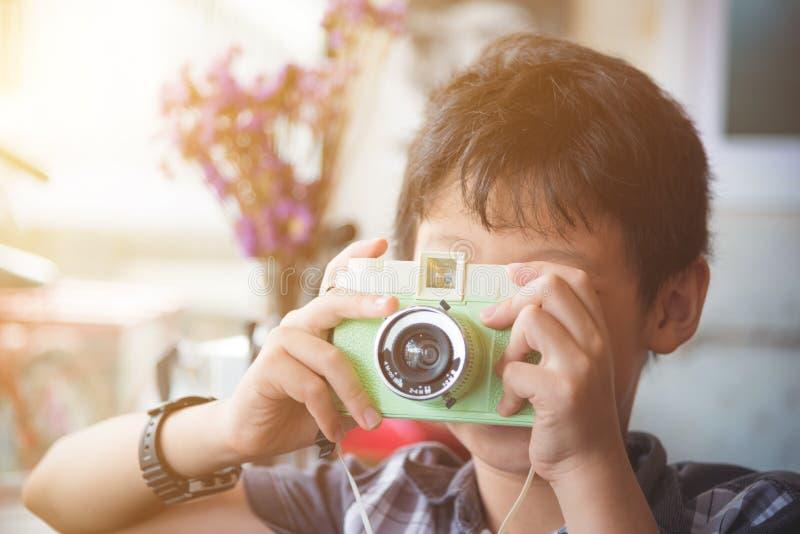 Pojke som tar fotoet vid den klassiska kameran med tappningfilt royaltyfri foto