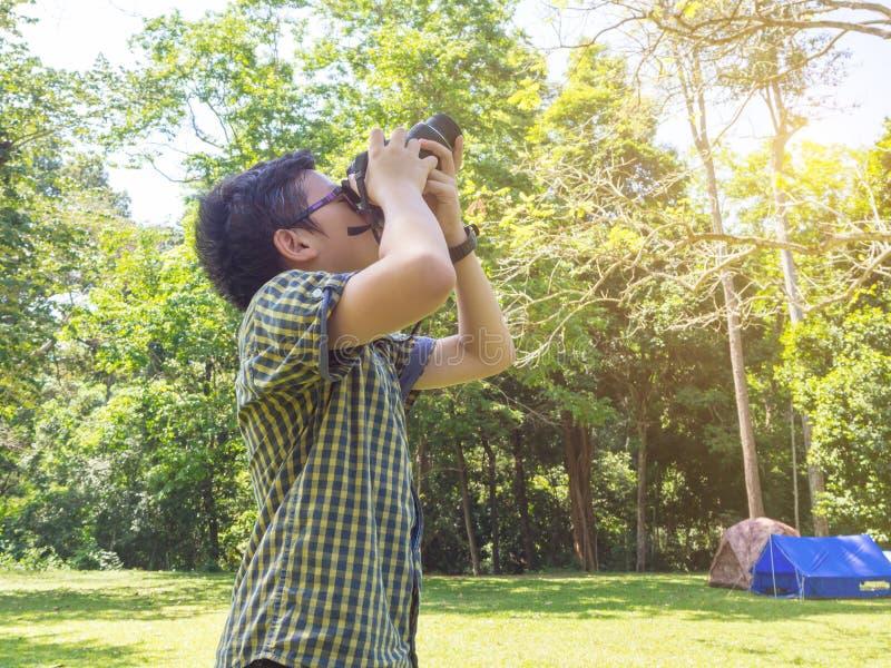 Pojke som tar fotoet vid kameran på den campa platsen i skog royaltyfria bilder