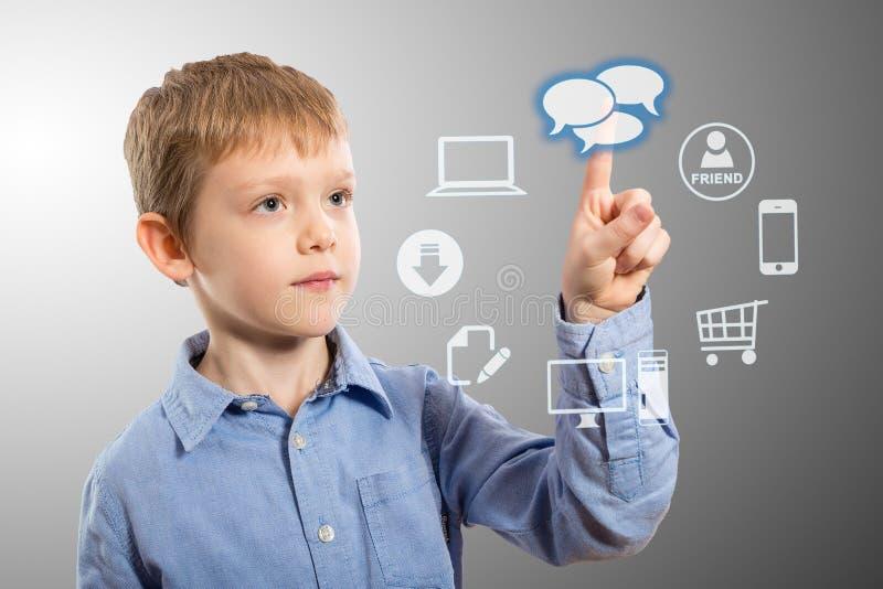Pojke som tar fram futuristiska underhållningapplikationer royaltyfria bilder