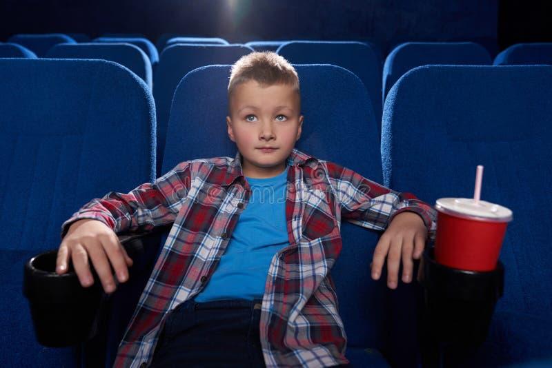 Pojke som uppmärksamt sitter i bioteatern, hållande ögonen på film royaltyfri bild