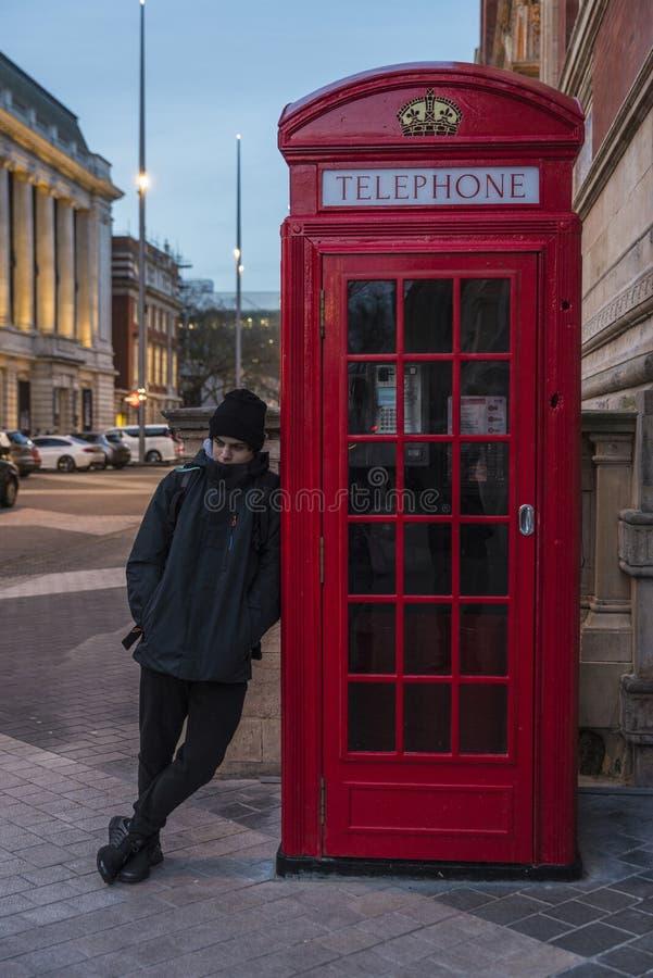Pojke som väntar på ett telefonbås i London, England, förenad konung arkivfoto