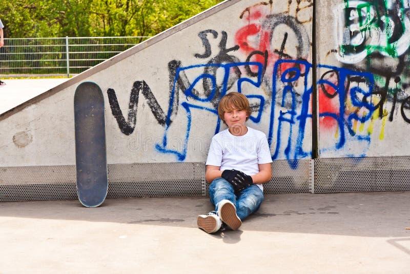 Pojke som vilar med skridskobrädet arkivbild
