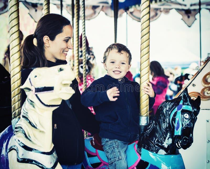 Pojke som vinkar på en karusellritt med den Retro modern - royaltyfri foto